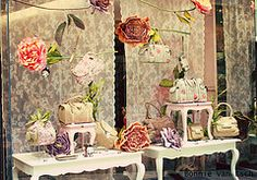 Shop Display in Blios, France.  fabric as backdrop - occassional tables for display stands