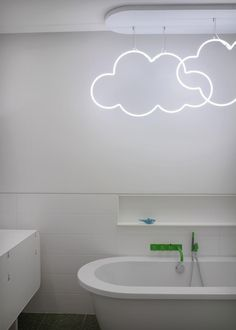 Neon lights shaped like clouds add a fun design element above the bathtub in…
