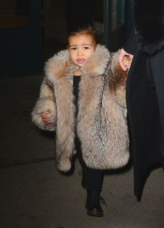 North West has a major glam moment while wearing an oversized fur coat to brace the cold temperatures in New York.    - HarpersBAZAAR.com