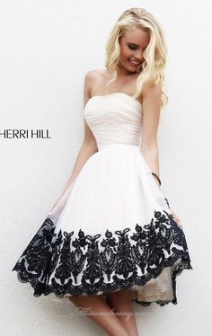 Surprise the crowd with Sherri Hill 11092, part of the Sadie Robertson by Sherri Hill collection. This glamorous cocktail dress features a strapless and straight neckline. Sheer bodice slims and flatters your shape. The flared skirt is adorned with floral embellishments along the short hemline.