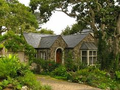 Dream cottage. Slate roof, rounded doorway, stone walls, copper-roofed bay, cobblestone drive, climbing roses, ferns...