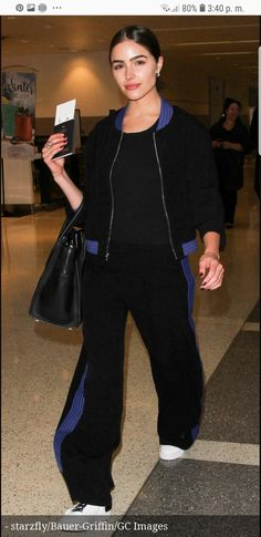 Prepare for the takeoff in a chic black tracksuit with royal blue piping  and a pair of black-laced white leather sneakers. e4eb41c3a