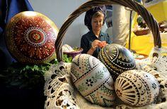 A woman in traditional Sorbian dress creates an Easter egg.