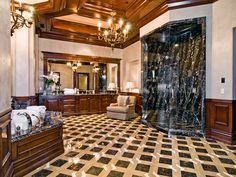 Magnificent master bath with contrasting dark stone shower against the wood in the ceilings and vanity.
