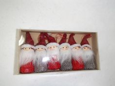 """Scandinavian Ornaments. Box of 6 adorable Santas ! Three in red and three in grey. Made with wooden base & heads, knit bodies and felt hats. They have a string loop for hanging. They measure 3"""". 