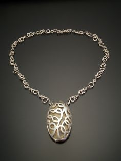 Jill Baker Gower.   I love the way the chain compliments the pendant.