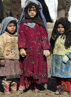 Afghan girls walk hand in hand in a refugee camp in Kabul