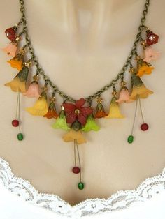 Beautiful, fall colored, Lucite flowers are featured in this long, handmade necklace. Genuine Swarovski Austrian crystals in light Colorado Topaz sit atop the filigree, antique brass, bead caps on ea
