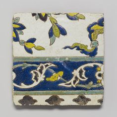 A Safavid cuerda seca fragmentary pottery Tile   Persia, 17th Century  square, decorated in blue, green, yellow, turquoise and black outline, all on a white ground, with a border enclosing meandering vines, the outer part with black rosettes and foliate sprays   24 cm. x 27 cm.
