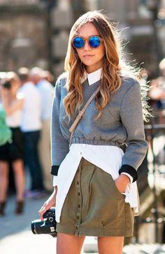 Street style look camisa branca, moletom cinza, saia botoes verde e óculos espelhado azul.