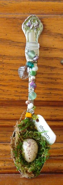 "Using a vintage spoon, I added wire and beads up the handle.   I added a silver ""dream"" tag and glass leaf among the beads.   In the cup of the spoon, I added moss and a half of a wooden egg that I painted to look like a birds egg. I made a wire loop on the back so the spoon can be hung."