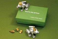 The box top says it best:  You're my Prince (Most of the time).  This paperweight comes with three interchangeable pieces of head gear:  a gold plated crown, ball cap, and dunce cap. Move them around to suit the mood your resident Prince creates in you! Cast in pewter. Measures approximately 2