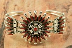 Genuine Red Coral set in Sterling Silver Bracelet. Beautiful Needle Point Design.  Created by Zuni Artist Dan Etsate. Signed by the artist. The Zuni Pueblo is located in New Mexico, Land of Enchantment.
