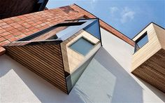The idiosyncratic, contemporary wood-lined dormer window on the street-facing facade blends with the original Victorian house, thanks to its use of natural materials