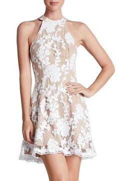 Fun and flirty short prom dress idea. Ladylike floral lace covers a fit-and-flare dress that's ready to party with after-hours sparkle. Love the balance of the high neckline and low-cut back.