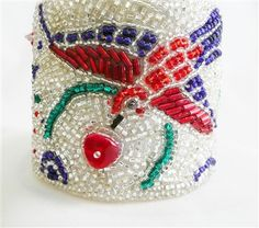 "This unique cuff displays colorful birds made from ruby, sapphire, and emerald Czech and Japanese Seed Beads, embroidered between silver-lined Seed Beads. Finished with a textured, white leather backing, and a silver-toned multi-strand slide lock tube clasp. Bracelet measures 8"" long and 2 ¼"" wide."