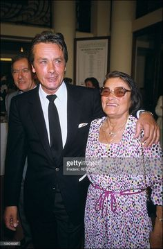 French actor Alain Delon is pictured with his mother as he receives the medal of Order of Arts and Letters from Jack Lang, French Culture Minister, on May 26, 1986 in Paris, France.