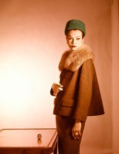 1959    Model is wearing a suit of tobacco-brown wool tweed with a Canadian lynx collar. Accented with emerald green velvet hat.