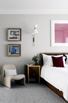Abstract wall art, grey walls, grey carpet, white bedding, red pillow, beige chair, white light fixture, and brown nightstand
