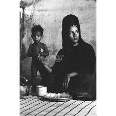 """Teatime  L'opera  proviene dall'archivio storico dell'agenzia """"D.F.P."""", fondata nel 1963 da Dina Maria Turriccia. Era il 1972 e i fotoreporters dell'agenzia """"D.F.P"""" indagano le condizioni sociali del paese africano, terra difficile e violenta, ma assolutamente affascinante. All'interno di una dimora una madre dal lungo abito nero accarezza dolcemente le mani del suo piccolo, sorpreso dal sopraggiungere del fotoreporter.  Africa, #Mauritania 1972."""