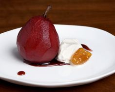 red wine poached seckel pears, served with orange and cinnamon flavored syrup, ice cream, and candied kumquats