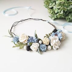 A delicate floral crown in calm tones of blue, with ivory and white flowers. The size of the wreath is adjustable with the ribbon. Lightweight and durable. ------------------------------------- Color: Shades of color may appear lighter or darker on different computer monitors.
