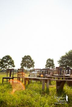 mismatched chairs and pews set in a field for an outdoor wedding ceremony