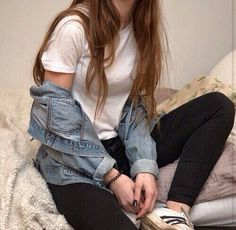 white t-shirt, light-wash jean jacket, black pants, and black and white adidas shoes