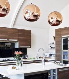 Walnut kitchen cabinets and copper globe pendants