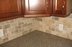View of granite quartz countertops with travertine backsplash and maple cabinets