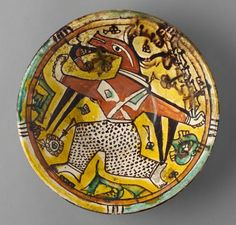 Bowl with Masked Dancing Figure Vessel 10th century Samanid period, AH 204-395 / AD 819-1005 Creation Place: Nishapur, Iran Reddish earthenware covered in whitish slip and painted with red (iron), black (manganese), green (copper), and yellow (stain from fine chromite particles) under clear lead glaze 8 x 26.8 cm (3 1/8 x 10 9/16 in.)