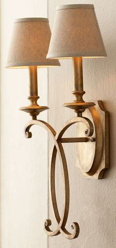 """Two-light sconce. Made of metal with a hand-applied silver-gold metallic finish. Linen hardback shades. Uses two 60-watt bulbs. Professional installation required. 13""""W x 8""""D x 24""""T. Imported. Boxed w"""
