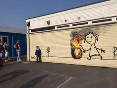 Trovano la facciata della scuola dipinta, ma non è il gesto di un vandalo: è l'ultimo murale di Banksy. L'opera è apparsa alla Bridge Farm primary school di Bristol (città natale di Bansky) ed è un omaggio agli studenti che hanno intitolato all'artista un'aula della struttura. Un ringraziamento inaspettato che ha lasciato genitori e bambini a bocca aperta. Così ora, accanto all'entrata, c'è un un grande bambino che gioca con una ruota in fiamme.