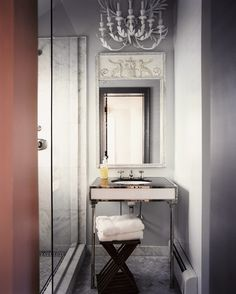 This petite bathroom abounds with luxurious elements, including gleaming chrome accents and a vintage neoclassical mirror.