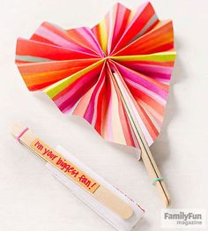 Fold an 8 1/2 - by 11-inch sheet of paper in half lengthwise, trace the template shape onto it, and cut it out. Unfold the paper, then accordion-fold it lengthwise, with each fold about 1/2- to 3/4-inch wide. Staple through the center of the folded paper. Glue a craft stick to either side of the staple on the longer side of the folded fan.                 When the glue is dry, open the fan by bringing the sticks together. Glue together the two flaps at the top of the heart. Write a message…