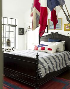 Don't be afraid to paint a vintage piece. Every piece of furniture can't be brown. In this bedroom by designer Dan Marty, French and British flags fly over an ebonized faux-bamboo bed.