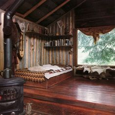 Rustic bohemian cabin bedroom. Industrial corrugated iron walls, lush timber floors, fireplace, lush furs  boho bedding.
