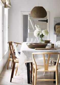 wishbone chairs, linen tablecloth, wicker, beautiful light, fresh flowers