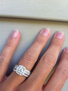 Cushion halo engagement ring with two wedding bands.