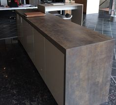 Island with waterfall in Iron Moss Neolith in The Ultimate Kitchen's showroom located in Vancouver, BC