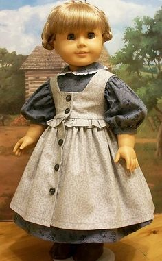 Kirsten Larson Hairstyle: *straight* loop braids Socks/Stockings: striped stockings Footwear: brown lace boots  Outfit:dress (short sleeve) pinafore (ruffled) Fabric: cotton and ruffled  Color:dress (bluish gray) pinafore (gray) Circa:1850s Used For: farming