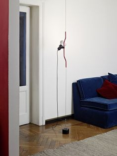 Parentesi by Achille Castiglioni and Pio Manzu complements this modern interior with red and navy accents and hardwood flooring.