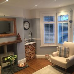 Stripped floorboards, wood burner, slate hearth, wooden beam, window shutters and arm chair. Cosy living room.