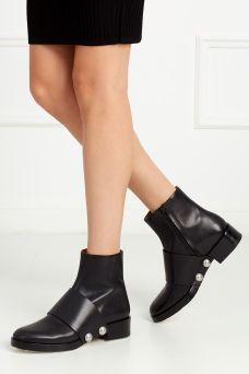Кожаные ботинки Hanne Alexander Wang. Ботинки в футуристическом стиле сделаны из натуральной кожи черного цвета. Каблук невысокий, устойчивый. Главным декоративным элементом служит широкий «ремень», украшенный крупными заклепками. Носим с легинсами, джинсами, подвернутыми брюками или, на контрасте, с платьями.