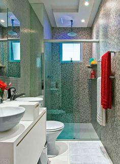 Um laminado decorativo com estampa abstrata reveste a parede do boxe deste banheiro projetado por Ricardo Umada. Na outra parede, ele optou por pastilhas de vidro em tom neutro. As fitas de led ao redor da ducha mudam de cor e permitem diferentes ambientações. Os acessórios de tom prateado harmonizam com o cinza predominante.