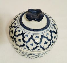 Hand painted round porcelain container, with a blue scalloped handle on top. This cute little covered bowl would be great as a covered candy dish,