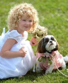 A little girl with gorgeous curls with her pet doggy...