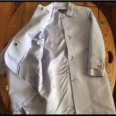 """NWOT Trench Coat Jacket In Periwinkle 🎉HP🎉 Beautifully styled, fully-lined 100% brushed cotton NWOT Periwinkle Spring Coat ~ 4 silver-tone bar & chain/grommet circle front closures & 2 front-sideway open pockets. Belted sleeves w/same closures (decorative purposes). Cute check print under collar (same on inside hang loop). Back vent still sewn /attached. Size P. Seam to seam: BUST under arms: 20""""; WAIST: 18"""" LENGTH from top of shoulder 34""""; SLEEVE LENGTH: 22-1/2"""". Smoke-free home…"""