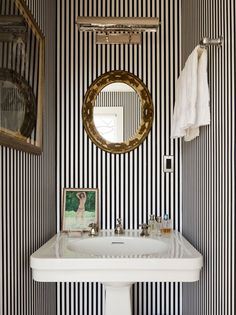 stripes, pedestal sink, small space, library light, propped art, black and white.
