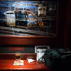 As commuters relax with a drink, train cars glide beneath the floor at Tracks Raw Bar & Grill. (Photo: Bryan Thomas for The New York Times)